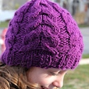 A knit flat cabled hat